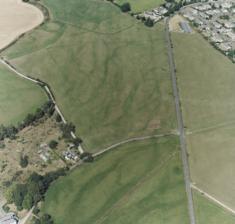 Dalginross, oblique aerial view, taken from the S, centred on the cropmarks of the Roman Temporary Camp. The Roman Fort is visible in the top centre of the photograph, and the cropmark of a road is shown in the botttom centre.