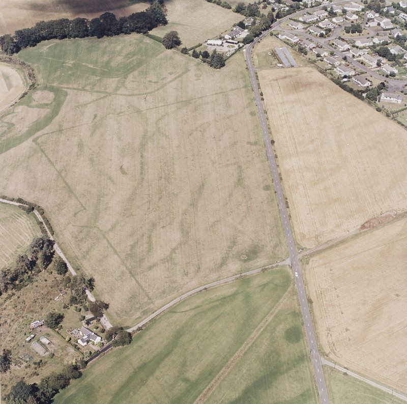 Dalginross, oblique aerial view, taken from the S, centred on the cropmarks of the Roman Temporary camp. The S corner of the Roman fort is visible in the top half of the photograph.