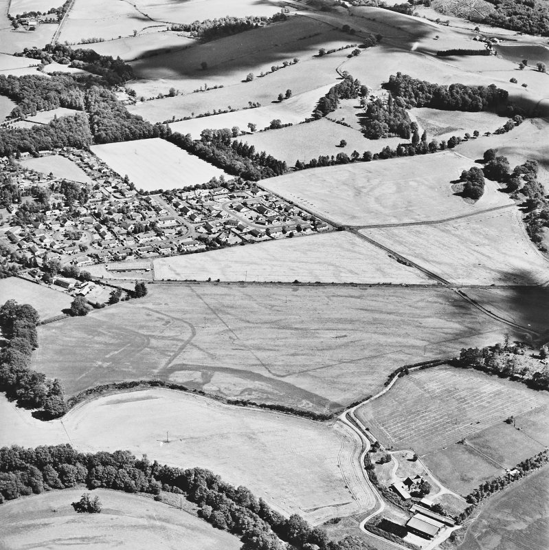 Dalginross, oblique aerial view, taken from the WNW, centred on the cropmarks of the Roman Temporary camp. The Roman fort is visible in the centre left of the photograph.