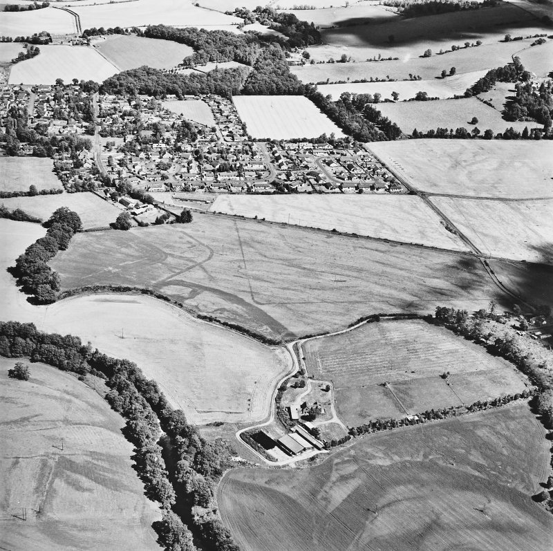 Dalginross, oblique aerial view, taken from the WSW, centred on the cropmarks of the Roman Temporary camp. The Roman fort is visible in the centre left of the photograph.