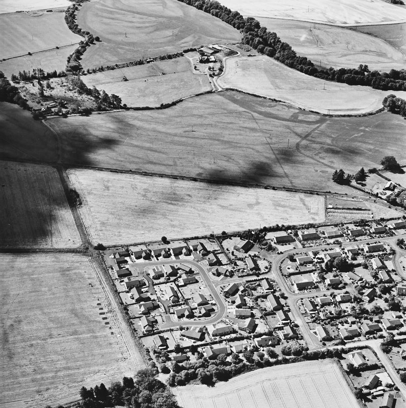 Dalginross, oblique aerial view, taken from the ENE, centred on the cropmarks of the Roman Temporary camp. The Roman fort is visible in the centre right of the photograph.