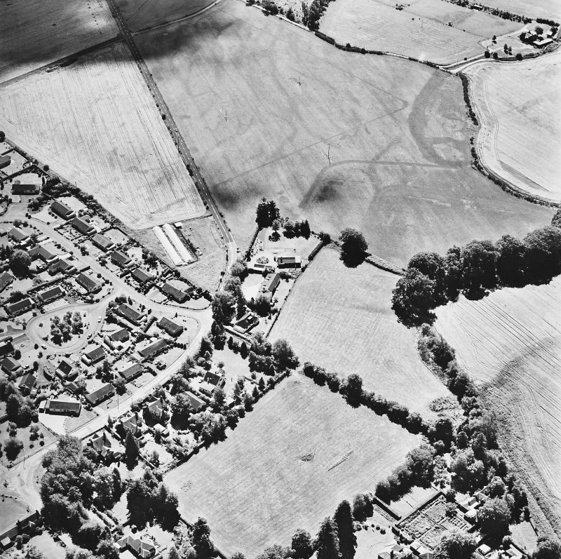 Dalginross, oblique aerial view, taken from the NNE, centred on the cropmarks of the Roman Fort. The Roman Temporary camp is visible in the top half of the photograph.
