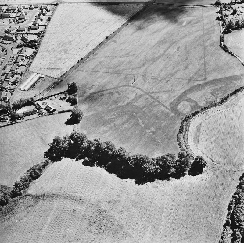 Dalginross, oblique aerial view, taken from the NNW, centred on the cropmarks of the Roman Fort. The Roman Temporary camp is visible in the top half of the photograph.