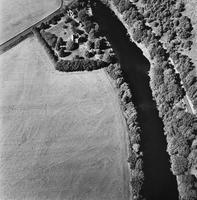 Comrie Castle, oblique aerial view, taken from the SE, centred on cropmarks including those of an enclosure. Comrie Castle is visible in the top centre of the photograph.