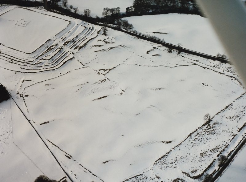 Oblique aerial view centred on temporary camps and fort under cover of snow.