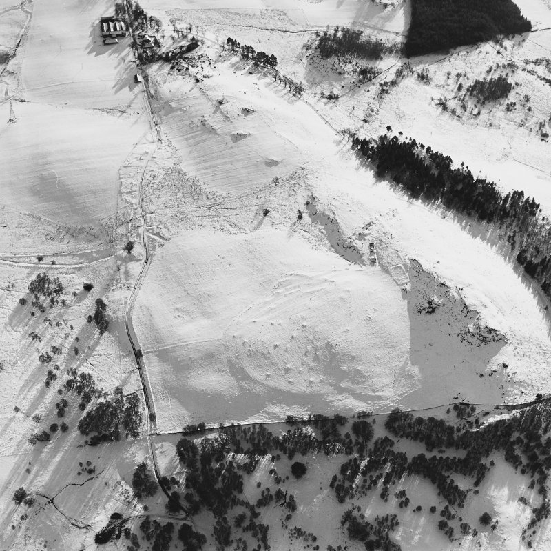 Oblique aerial view centred on the remains of the small cairns and farmstead with the remains of the township, the cottage and the farmsteading adjacent, taken from the NNE.