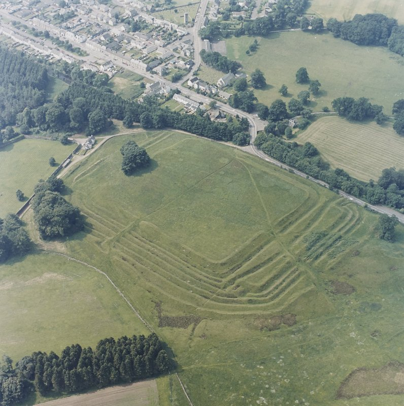 Oblique aerial view centred on the remains of the Roman Fort, chapel and burial ground, with road bridge adjacent, taken from the ENE.