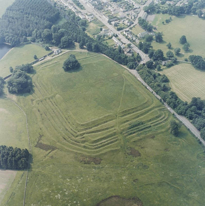 Oblique aerial view centred on the remains of the Roman Fort, chapel and burial ground, with road bridge adjacent, taken from the NE.