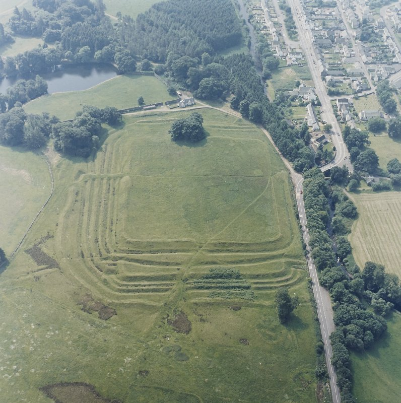 Oblique aerial view centred on the remains of the Roman Fort, chapel and burial ground, with road bridge adjacent, taken from the NNE.