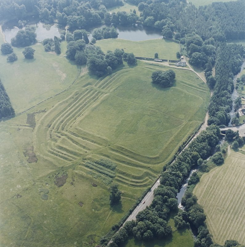 Oblique aerial view centred on the remains of the Roman Fort, chapel and burial ground, with road bridge adjacent, taken from the NNW.