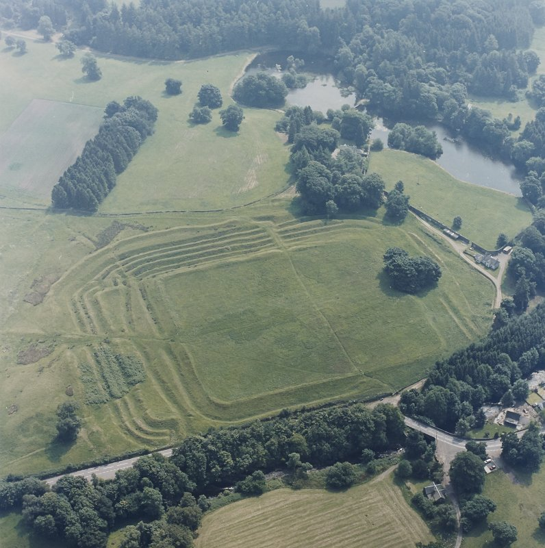 Oblique aerial view centred on the remains of the Roman Fort, chapel and burial ground, with road bridge adjacent, taken from the WNW.