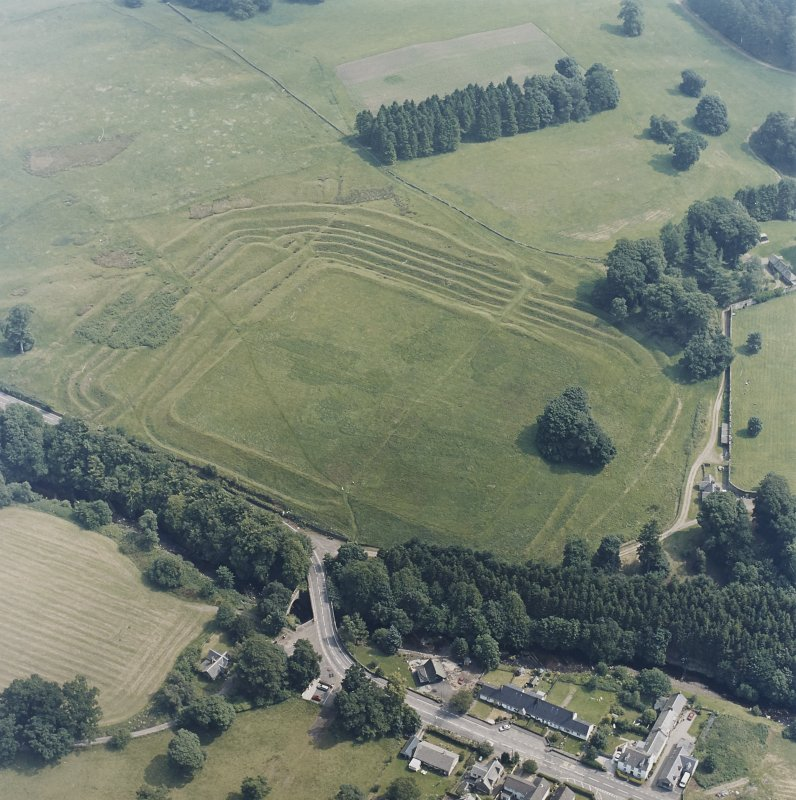 Oblique aerial view centred on the remains of the Roman Fort, chapel and burial ground, with road bridge adjacent, taken from the WSW.