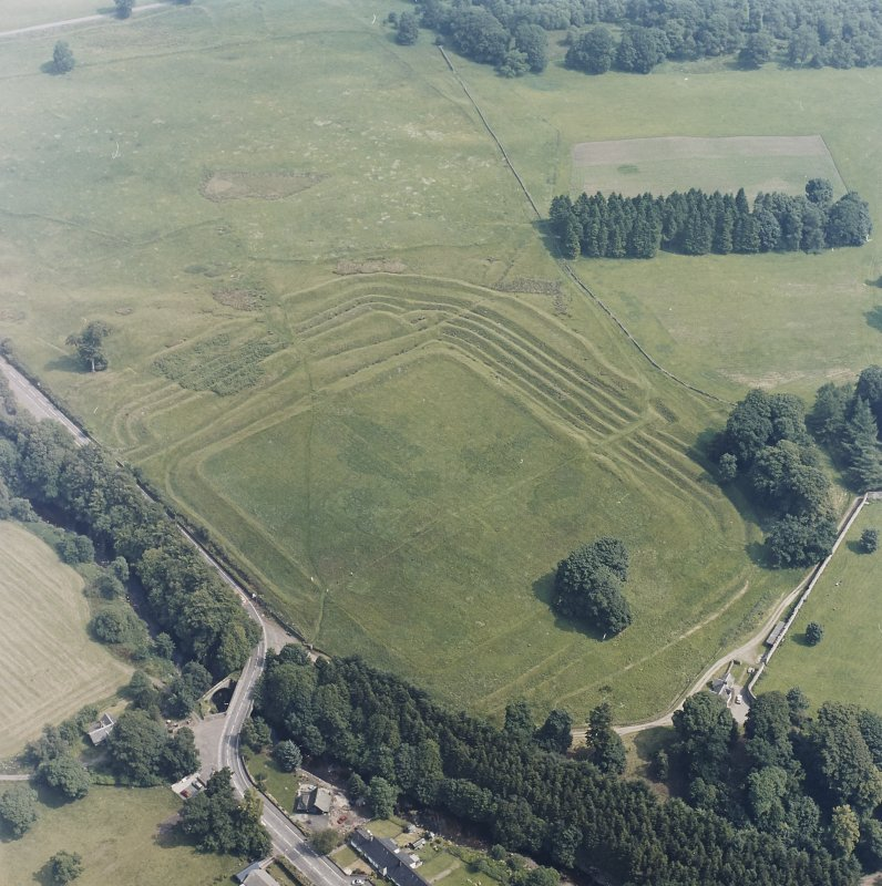 Oblique aerial view centred on the remains of the Roman Fort, chapel and burial ground, with Roman Temporary Camp and road bridge adjacent, taken from the SW.