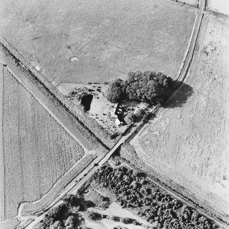 Inchaffray Abbey, oblique aerial view, taken from the SE, centred on the remains of the abbey. A road bridge is visible in the bottom centre of the photograph.