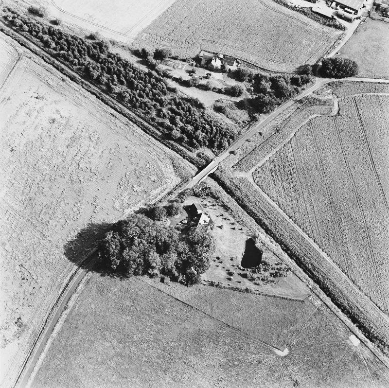 Inchaffray Abbey, oblique aerial view, taken from the NW, centred on the remains of the abbey. A road bridge is visible in the centre of the photograph.