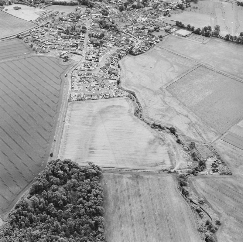 Oblique aerial view of Dunning centred on the cropmarks of a Roman temporary camp and the village, taken from the NNE.