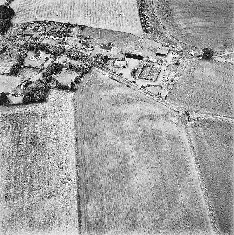 Forteviot, oblique aerial view, taken from the SSE, centred on cropmarks including those of an enclosure, a barrow cemetery and pit-alignments. Forteviot village is visible in the top half of the photograph.