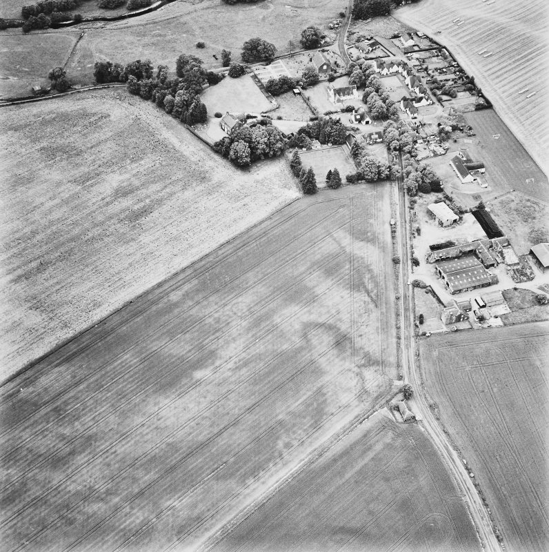 Forteviot, oblique aerial view, taken from the ESE, centred on cropmarks including those of an enclosure, a barrow cemetery and pit-alignments. Forteviot village is visible in the top right-hand corner of the photograph.