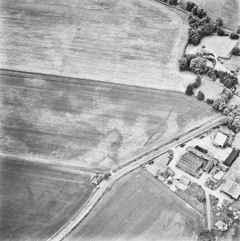 Forteviot, oblique aerial view, taken from the ENE, centred on cropmarks including those of an enclosure, a barrow cemetery and pit-alignments. Farm of Forteviot and Forteviot Manse are visible in the right half of the photograph.