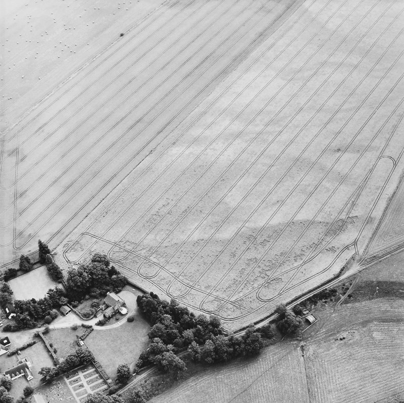 Oblique aerial view centred on the cropmarks of the enclosures with the manse adjacent, taken from the W.