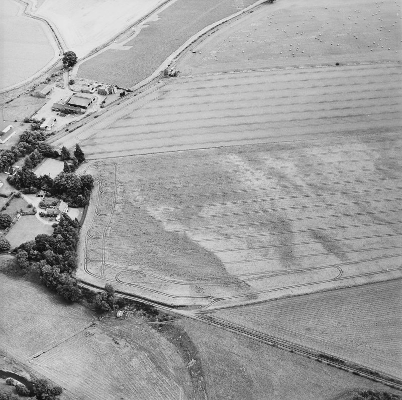 Oblique aerial view centred on the cropmarks of the enclosures with the manse adjacent, taken from the WSW.