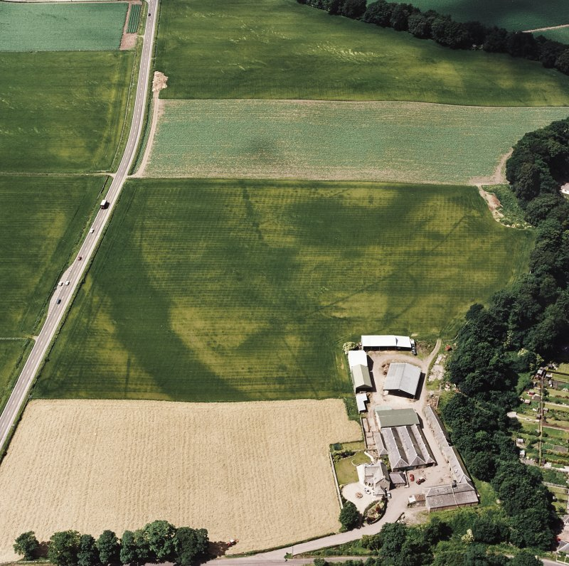 Oblique aerial view centred on the cropmarks of an enclosure, pit-circle, Roman Road, linear cropmarks, pits and pit-alignment, taken from the ENE.