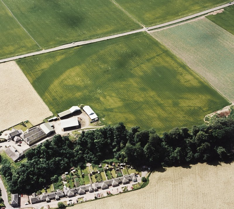 Oblique aerial view centred on the cropmarks of an enclosure, pit-circle, Roman Road, linear cropmarks, pits and pit-alignment with linear cropmarks adjacent, taken from the NNE.