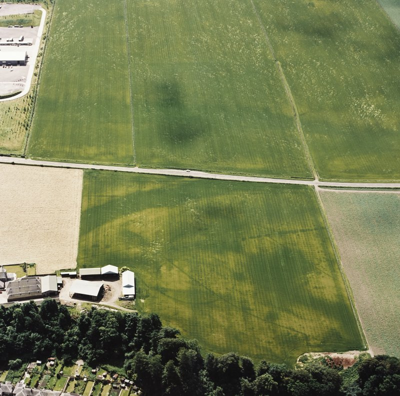 Oblique aerial view centred on the cropmarks of an enclosure, pit-circle, Roman Road, linear cropmarks, pits and pit-alignment with linear cropmarks adjacent, taken from the N.