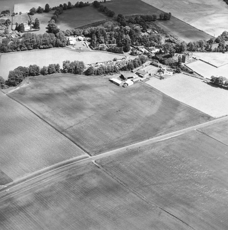 Oblique aerial view centred on the cropmarks of an enclosure, pit-circle, Roman Road, linear cropmarks, pits and pit-alignment with linear cropmarks and castle adjacent, taken from the SSW.