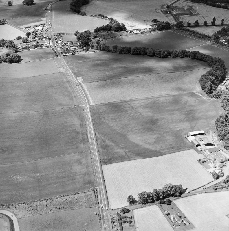 Oblique aerial view centred on the cropmarks of an enclosure, pit-circle, Roman Road, linear cropmarks, pits and pit-alignment with linear cropmarks adjacent, taken from the E.