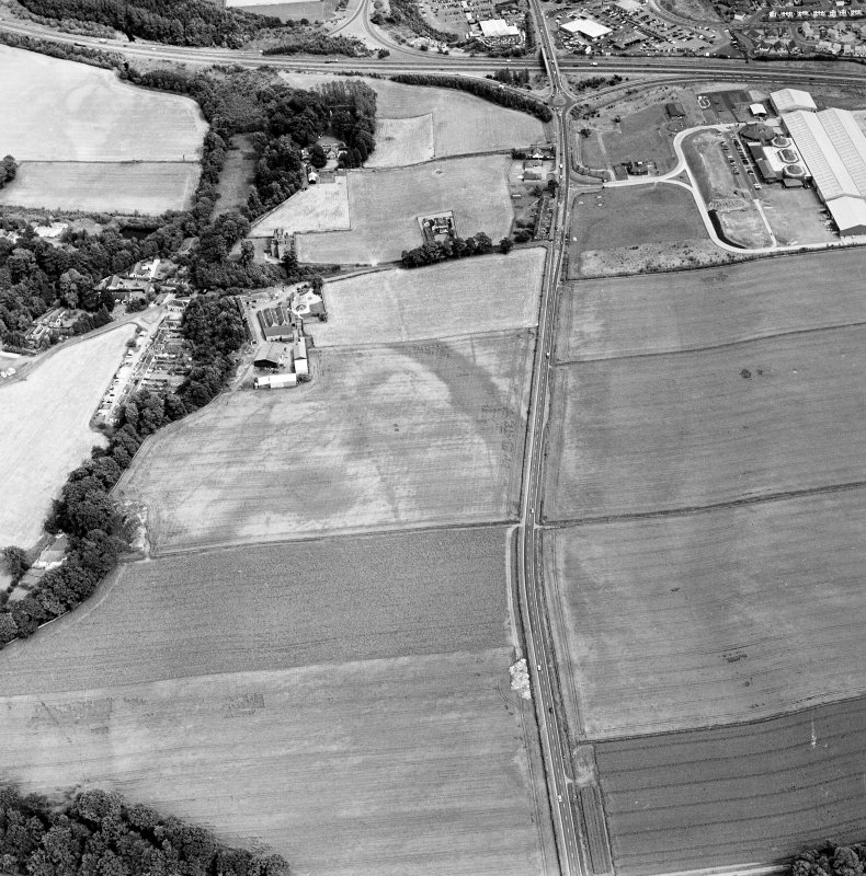 Oblique aerial view of Huntingtower and Huntingtower Mains centred on the cropmarks of a Roman road, enclosure, pit-circle, pits and various linear cropmarks and miscellaneous cropmarks, taken from the WNW.