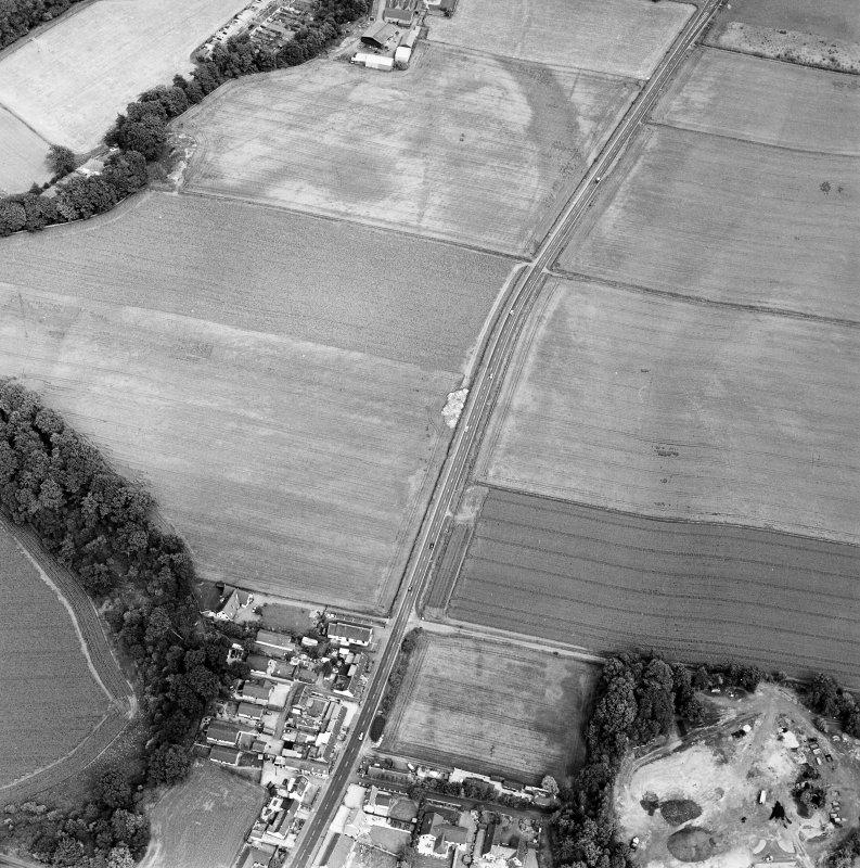 Oblique aerial view of Huntingtower and Huntingtower Mains centred on the cropmarks of a Roman road, enclosure, pit-circle, pits and various linear cropmarks and miscellaneous cropmarks, taken from the WSW.