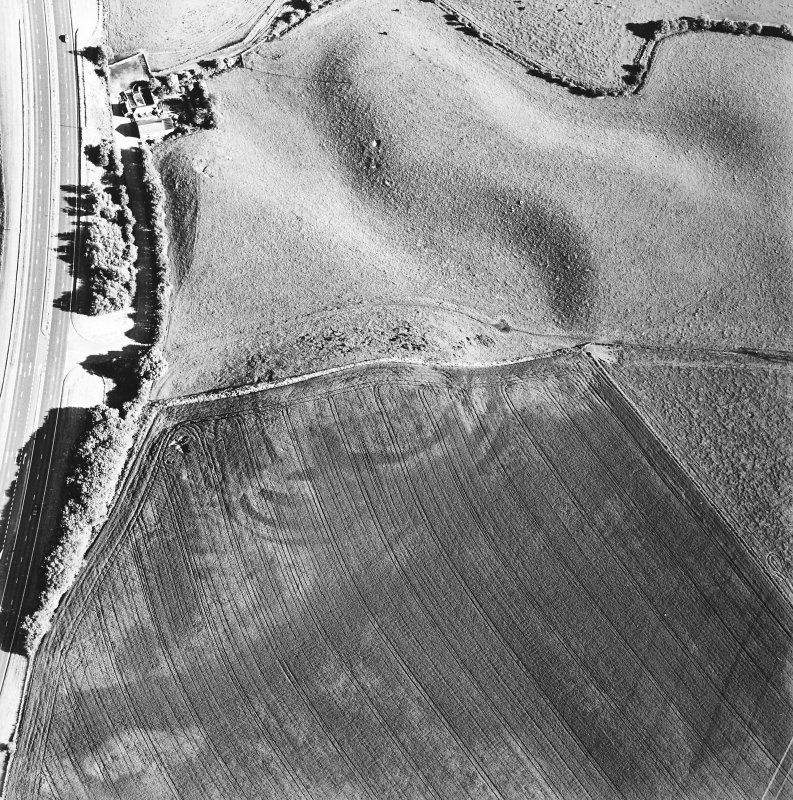 Oblique aerial view of Broxy Kennels centred on the cropmarks of a fort, taken from the NW.