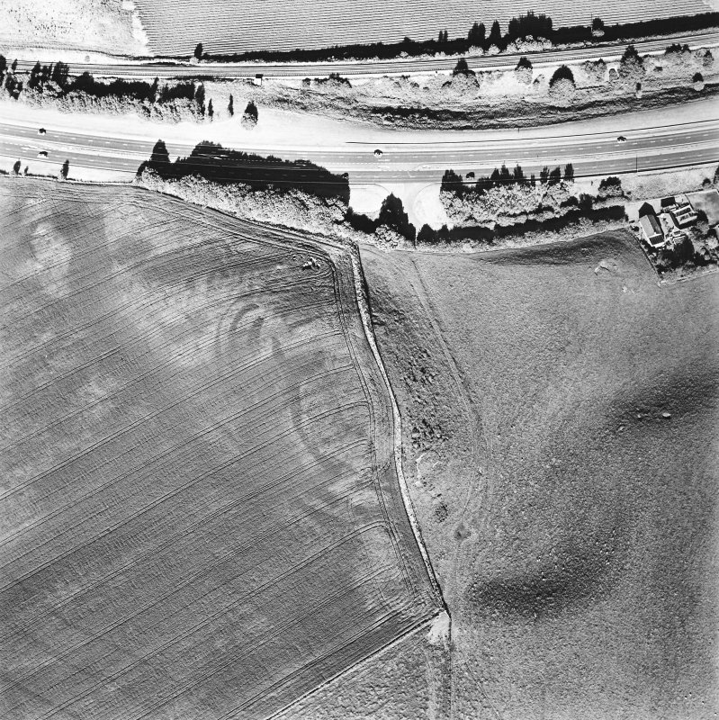 Oblique aerial view of Broxy Kennels centred on the cropmarks of a fort, taken from the W.