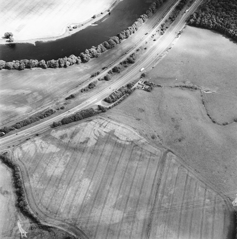 Oblique aerial view centred on the cropmarks of the fort, taken from the NW.