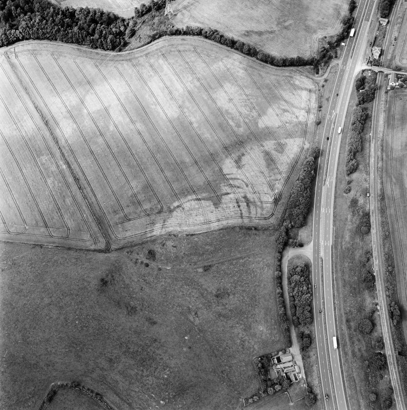 Oblique aerial view centred on the cropmarks of the fort, taken from the SSE.