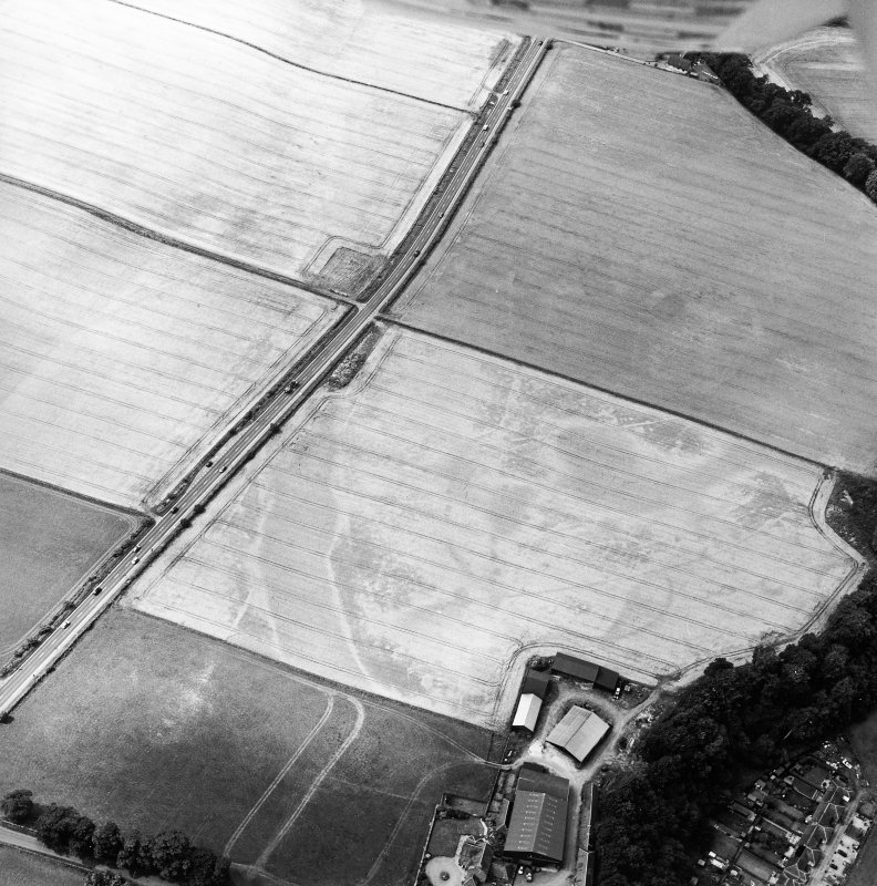 Oblique aerial view of the cropmarks of the enclosure, pits, ring-ditch, pit-alignment and Roman Road, taken from the ENE.