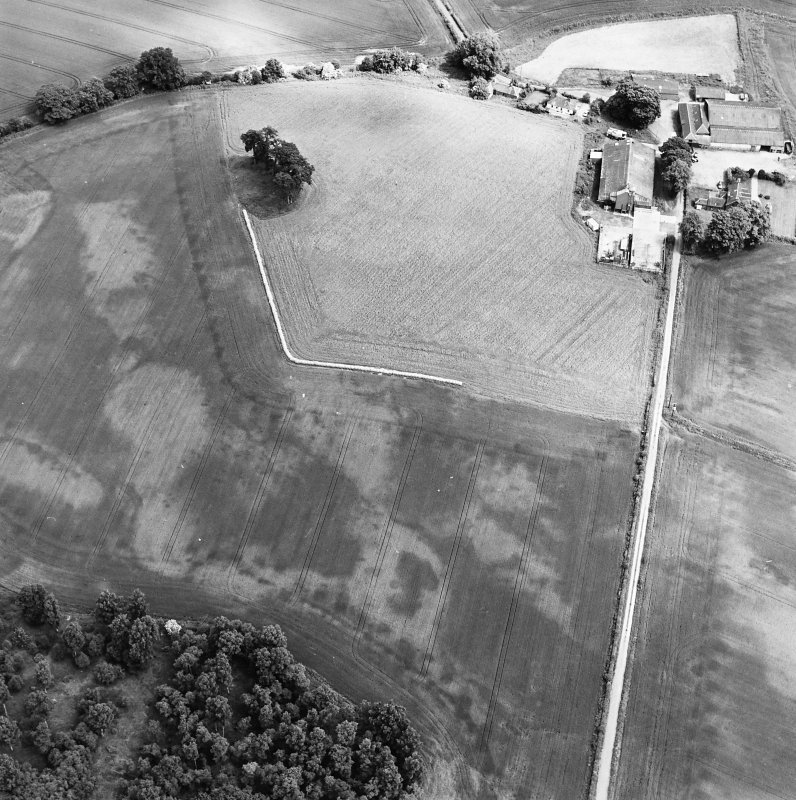 Oblique aerial view centred on the cropmarks of an unenclosed settlement with natural feature adjacent, taken from the SW.