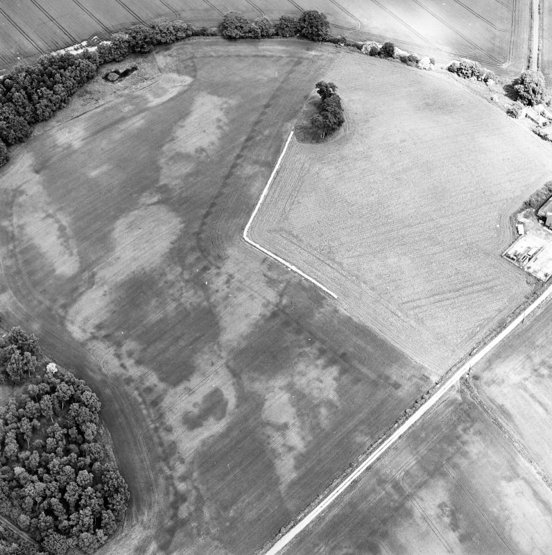 Oblique aerial view centred on the cropmarks of an unenclosed settlement with natural feature adjacent, taken from the SSW.
