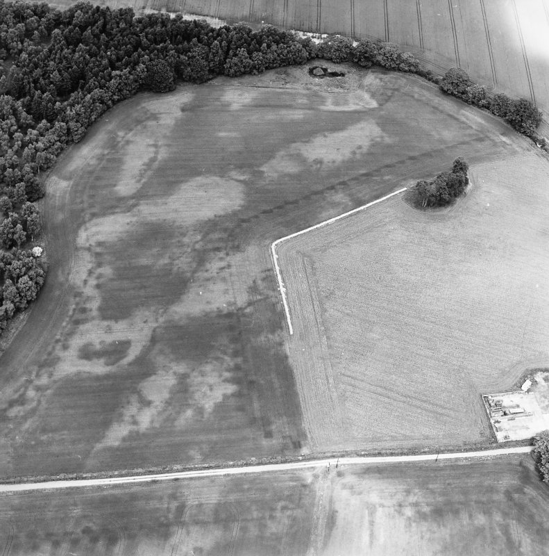 Oblique aerial view centred on the cropmarks of an unenclosed settlement with natural feature adjacent, taken from the SSE.