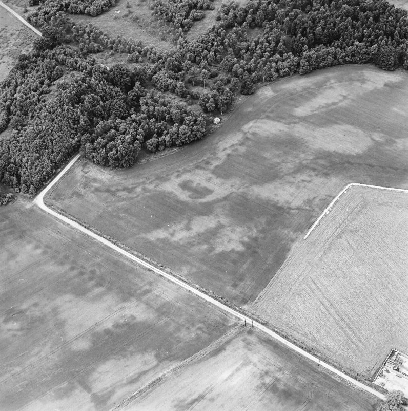 Oblique aerial view centred on the cropmarks of an unenclosed settlement with natural feature adjacent, taken from the SE.