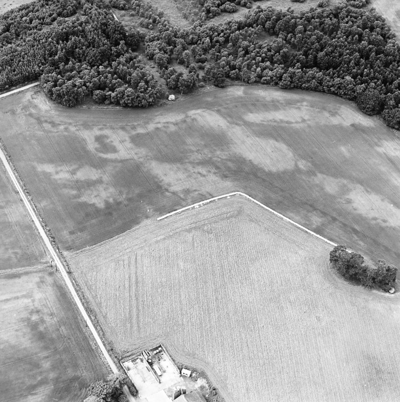 Oblique aerial view centred on the cropmarks of an unenclosed settlement with natural feature adjacent, taken from the E.