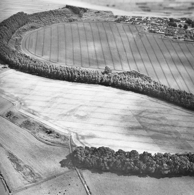 Oblique aerial view centred on the cropmarks of the palisaded enclosure, ring-ditch, Roman road, round house, souterrain, pits, linear cropmark and possible pit-alignment, taken from the NW.