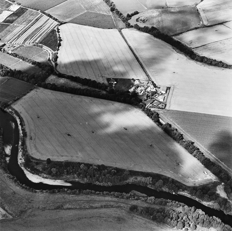 Oblique aerial view centred on the site of a pit-defined cursus and enclosure, taken from the SE.