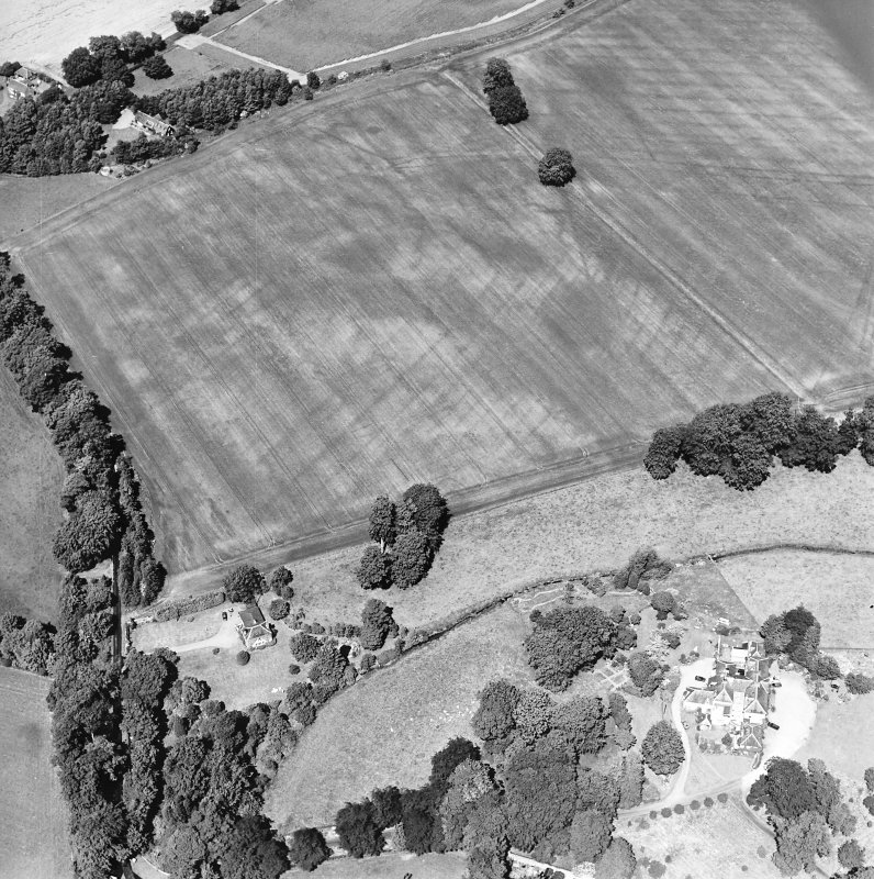 Oblique aerial view centred on the cropmarks of rig and possible timber halls with rectiliear enclosure, field boundaries, ice house, farmsteading, house and country house adjacent, taken from the SSE.