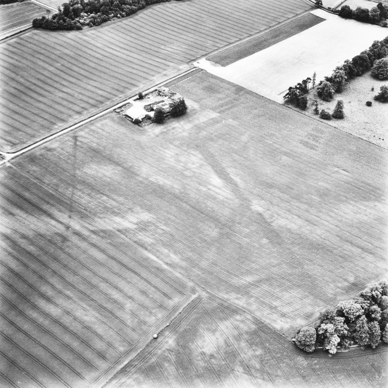 Carpow and Gillies Burn, oblique aerial view, taken from the NE, centred on the cropmarks of a Roman Fort, a Roman enclosure and an unenclosed settlement. The cropmarks of a Roman aqueduct and a ring-ditch, and Mains of Carpow farmsteading are visible in the top half of the photograph, and linear cropmarks are shown in the bottom centre half.