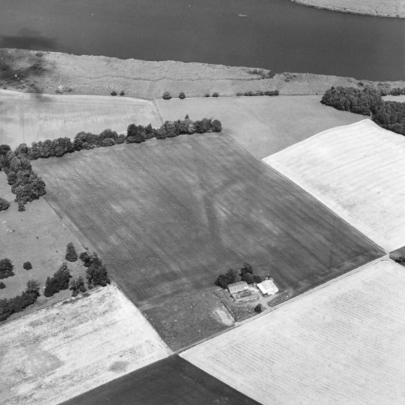 Oblique aerial view centred on the cropmarks of the E and S ditches of the Roman Fortress, with the farmsteading adjacent, taken from the S.