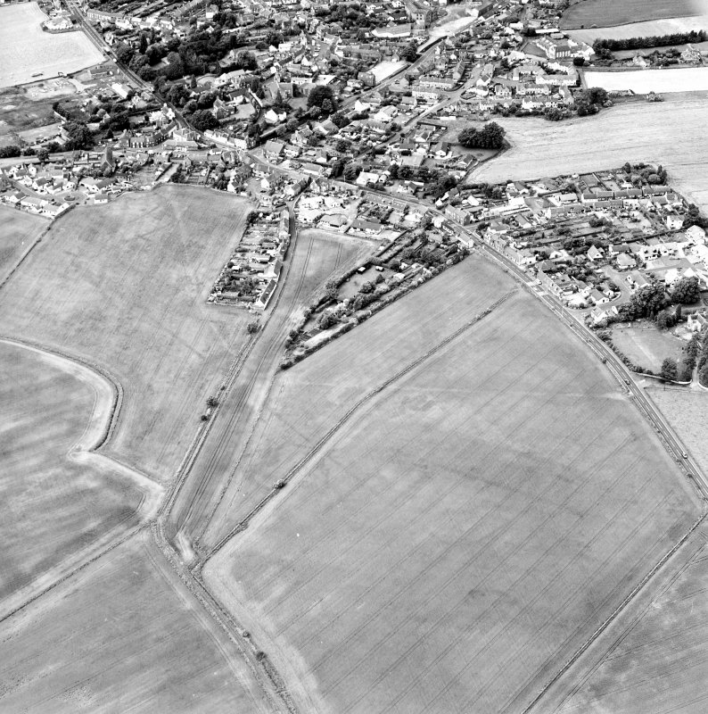 Oblique aerial view centred on the cropmarks of the S end of the Roman Temporary Camp with possible unenclosed settlements and town adjacent, taken from the E.