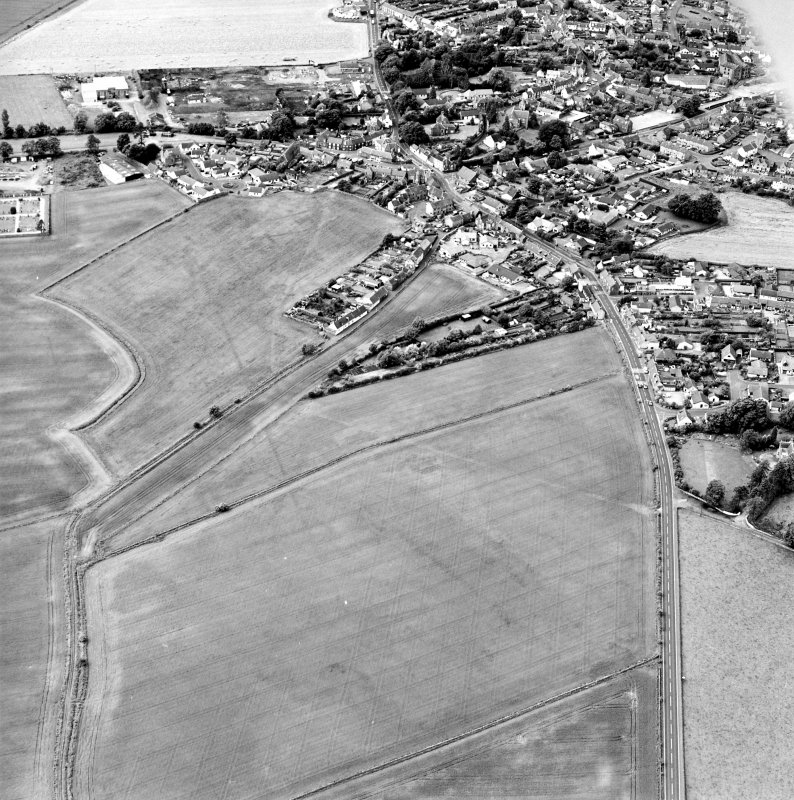 Oblique aerial view centred on the cropmarks of the S end of the Roman Temporary Camp with possible unenclosed settlements and town adjacent, taken from the ENE.