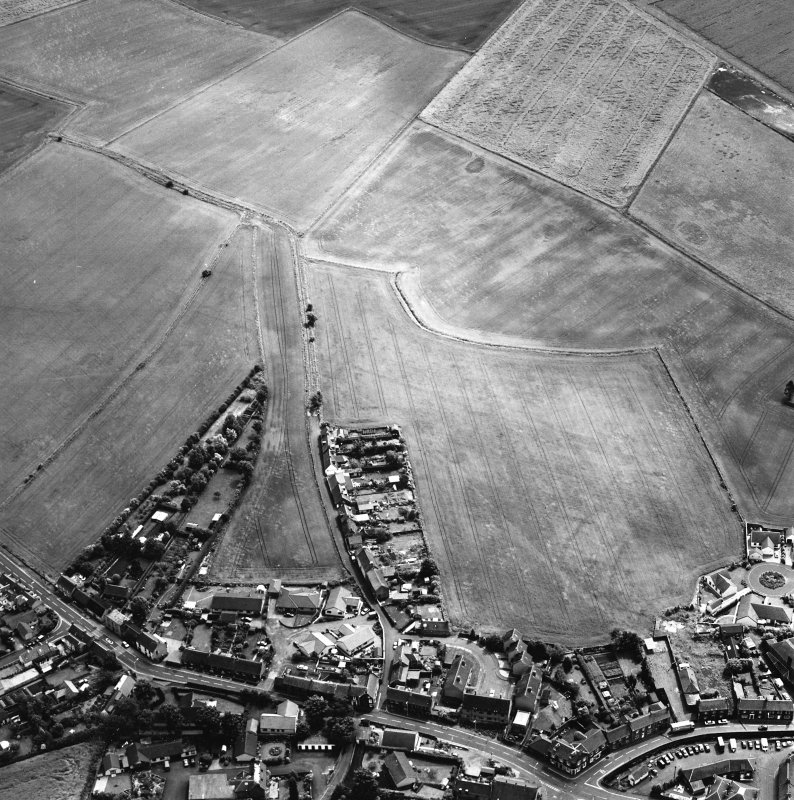 Oblique aerial view centred on the cropmarks of the S end of the Roman Temporary Camp with possible unenclosed settlements and town adjacent, taken from the NW.